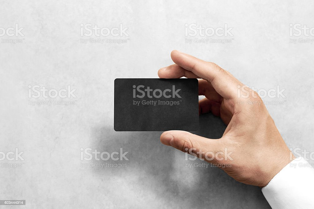 Hand hold blank black craft card mockup with rounded corners stock photo