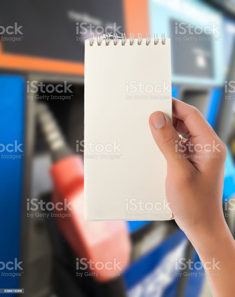 Hand hold blank notepad with Blur fuel dispenser stock photo