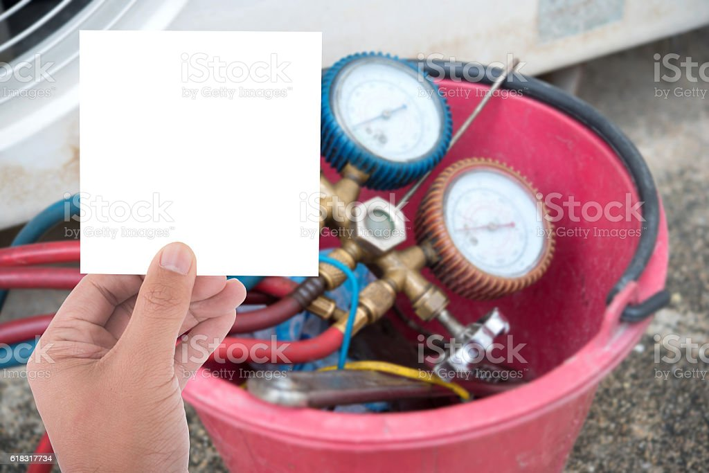 hand hold blank paper on detail of Air Conditioning installation stock photo