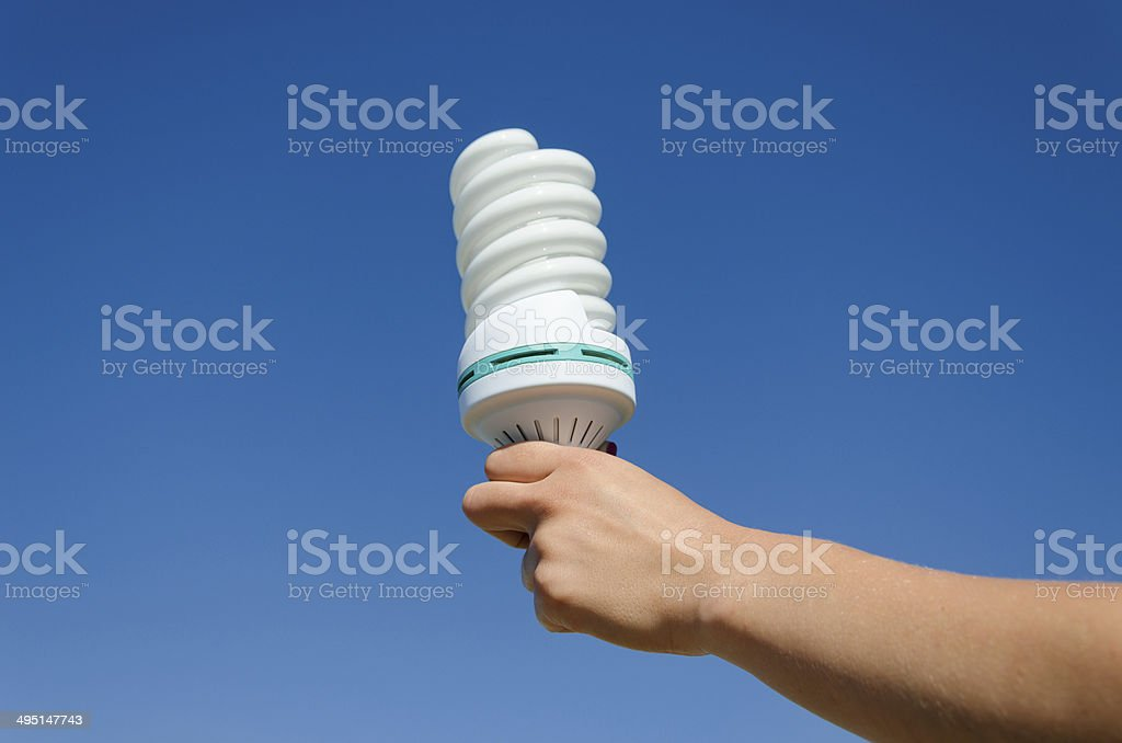 hand hold ecology save bulb on blue sky background stock photo