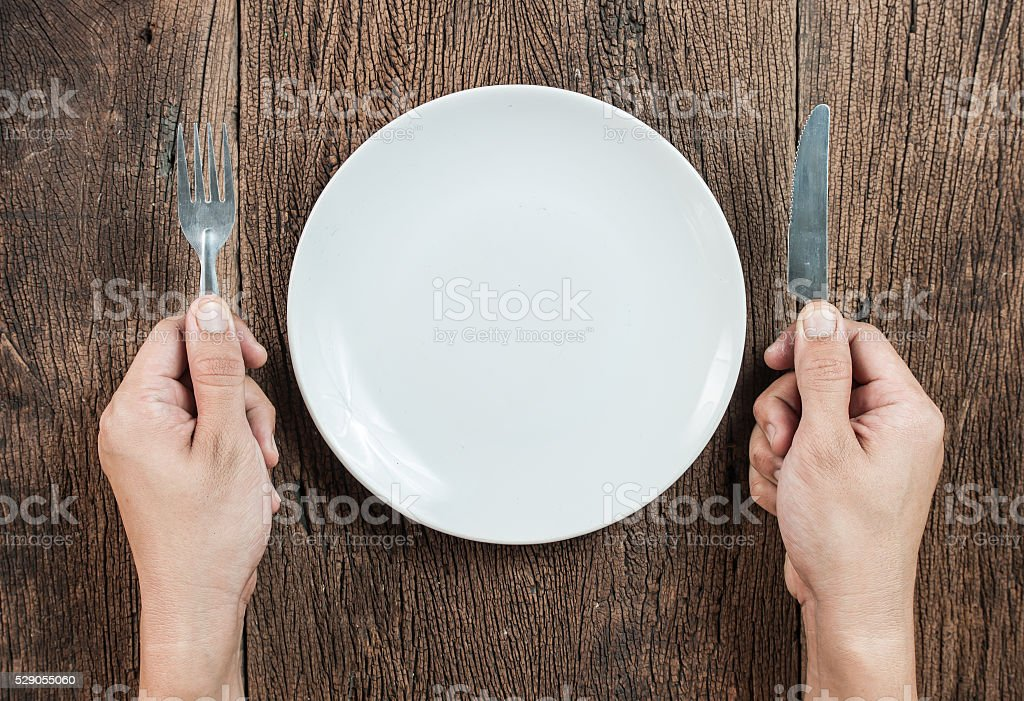 Hand hold fork and knife with plate on wood stock photo