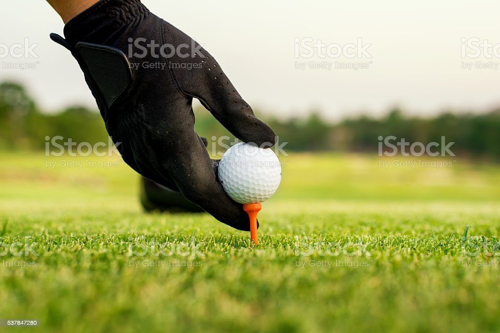 Hand hold golf ball with tee on course, close-up stock photo
