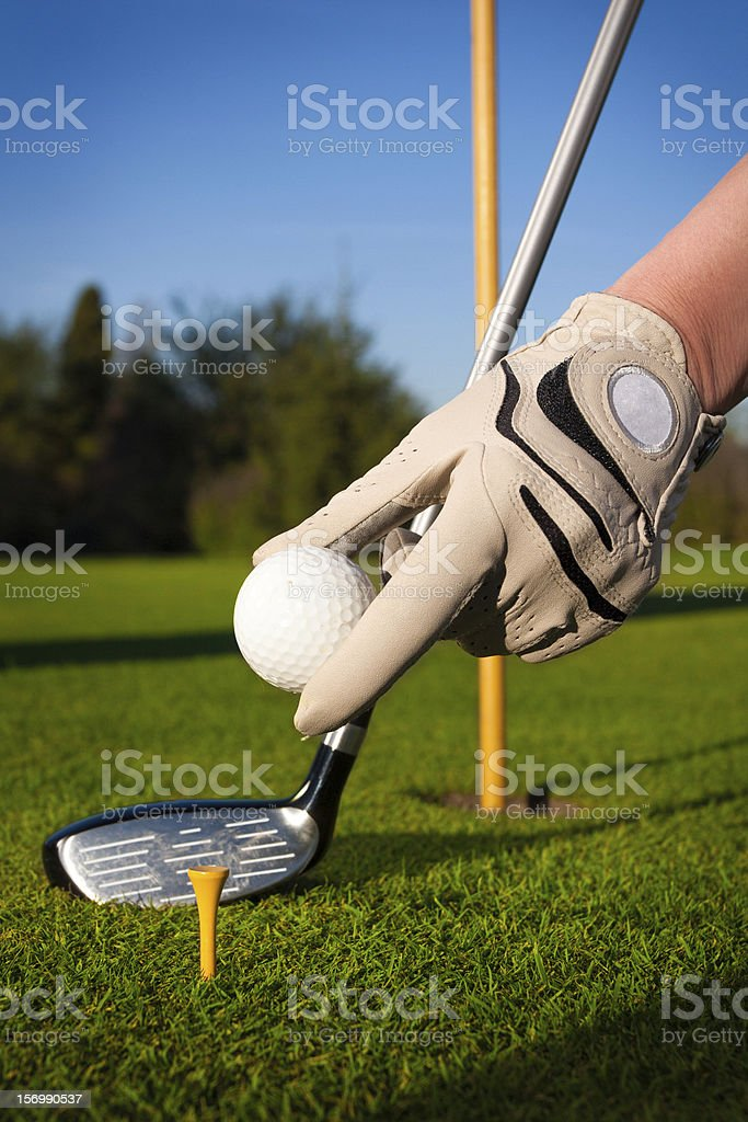 Hand hold golf ball with tee on course royalty-free stock photo