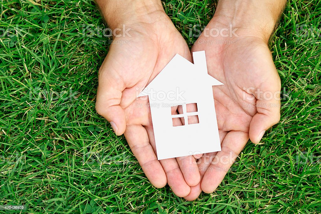 Hand hold house against green field stock photo