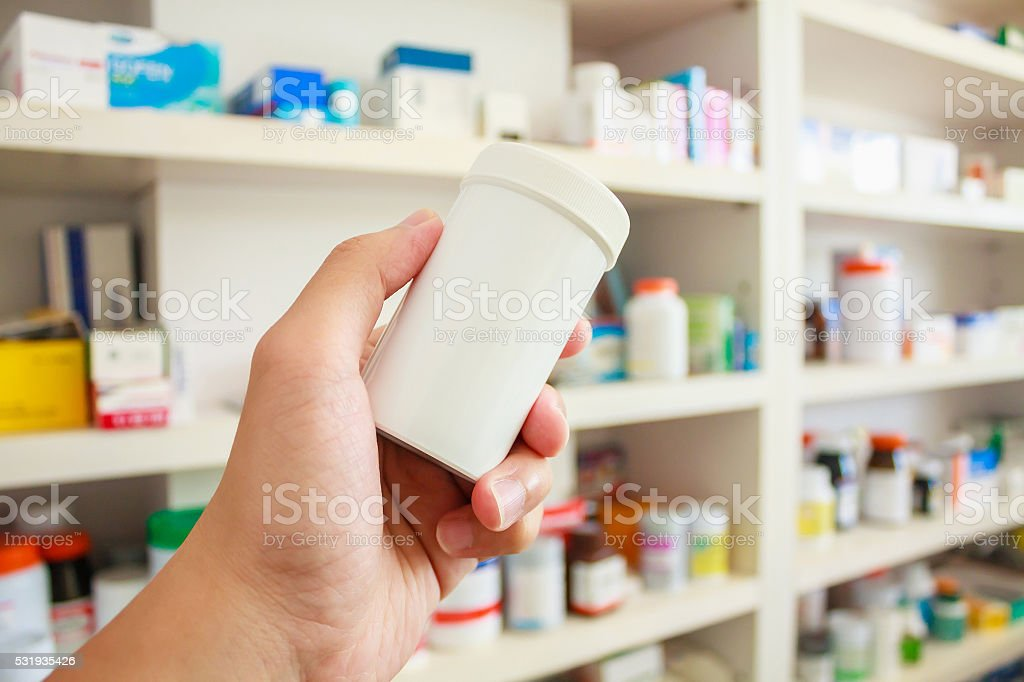 hand hold medicine bottle in the pharmacy stock photo