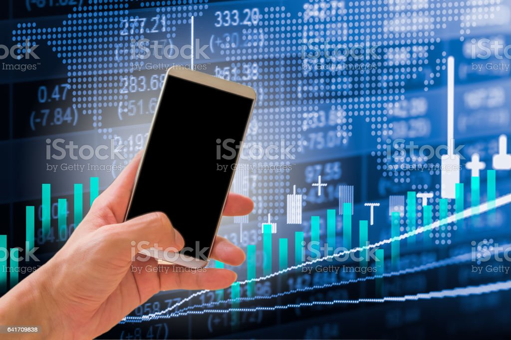 Hand hold smart phone on stock market indicator and stock photo