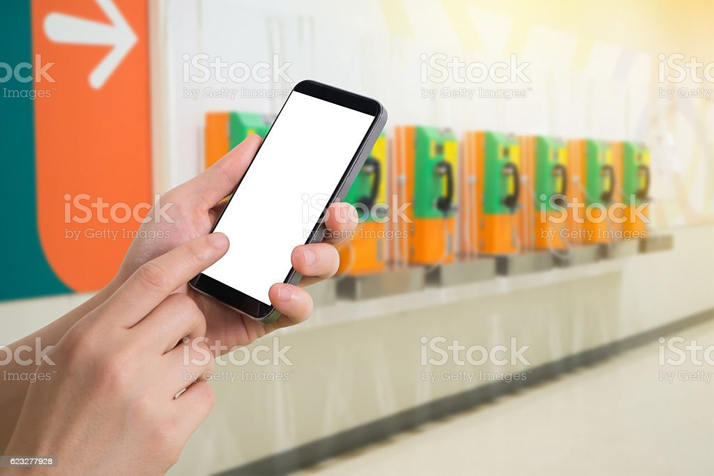 hand hold smartphone on blurry obsolete phone booth. stock photo
