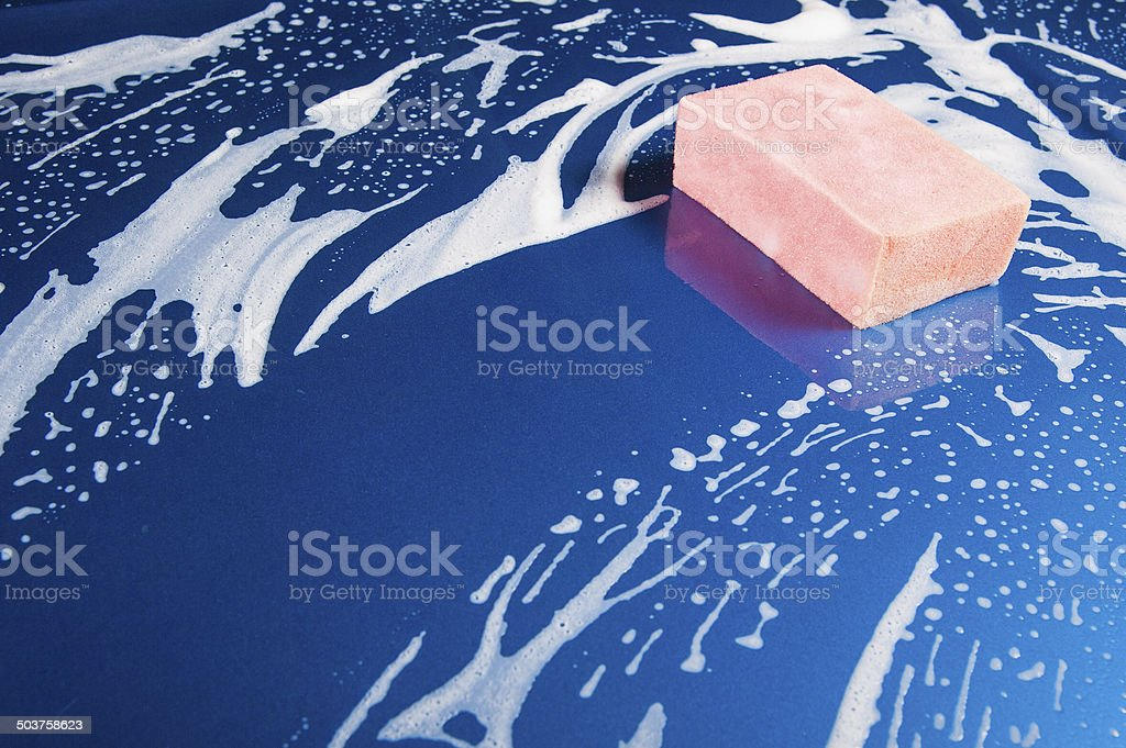 hand hold sponge over the car for washing stock photo