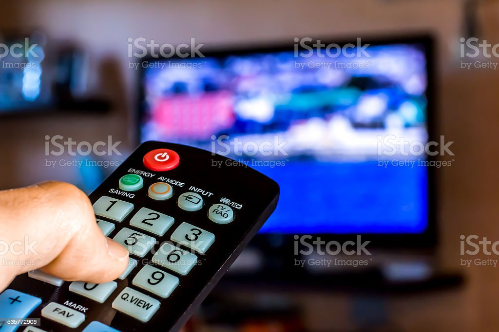 Hand hold the remote control to change channels on Tv stock photo