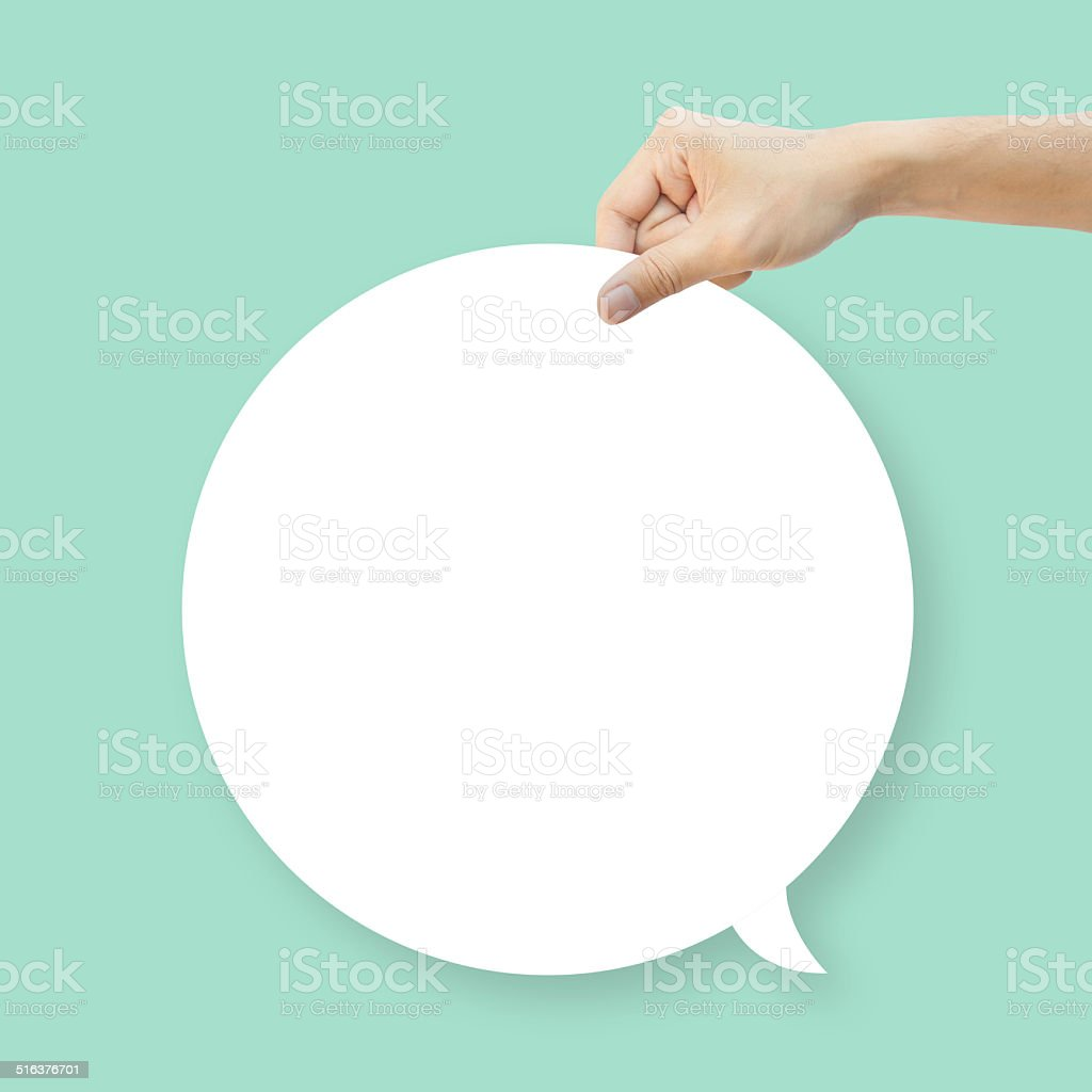 Hand hold white bubble quote chat on green background stock photo