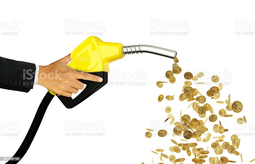 Hand holdind Fuel nozzle pouring with golden coin stock photo
