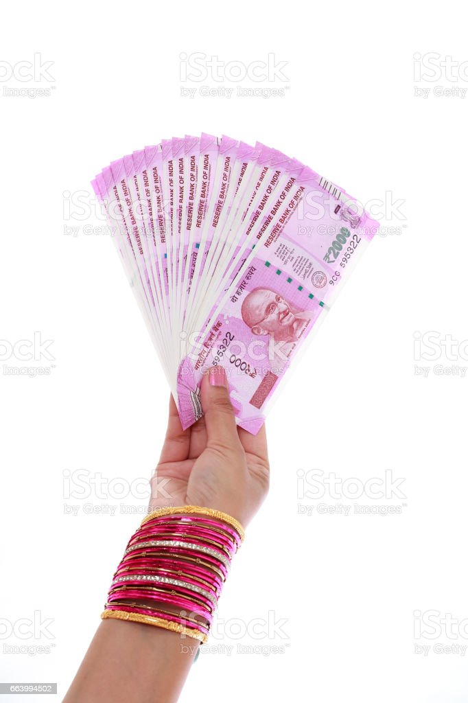 Hand holding 2000 rupee notes against white background stock photo