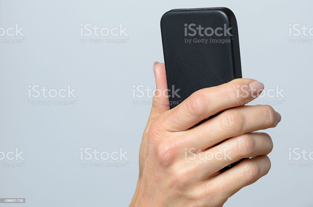 Hand holding a black cellular stock photo