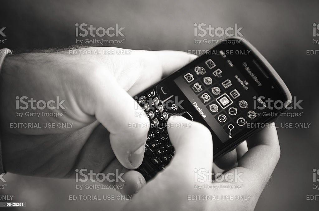 Hand holding a Blackberry smartphone with facebook.com apps royalty-free stock photo