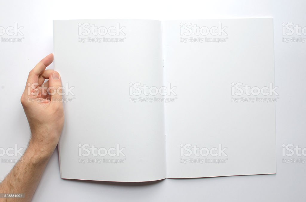 Hand holding a blank brochure with copy space stock photo