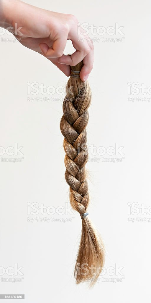 Hand holding a braided ponytail cut off for making wig royalty-free stock photo