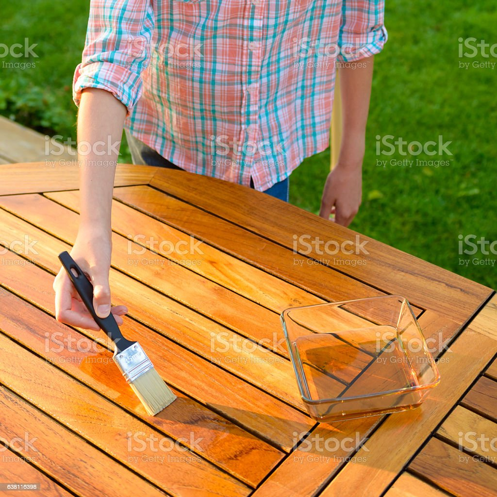 hand holding a brush applying varnish on a garden table stock photo