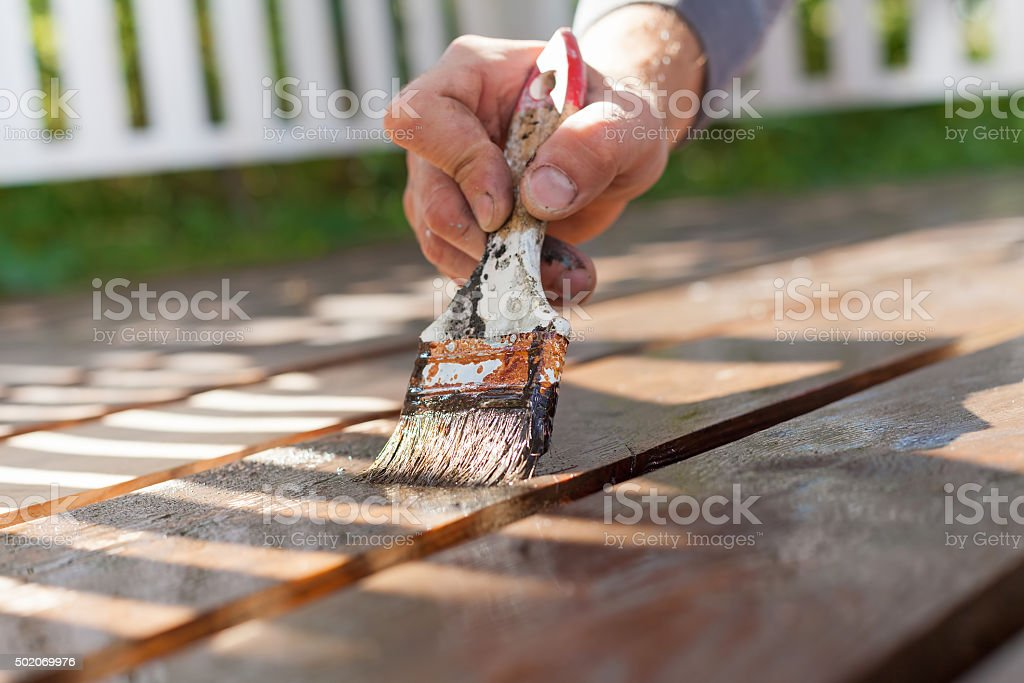 hand holding a brush applying varnish paint on wooden surface stock photo