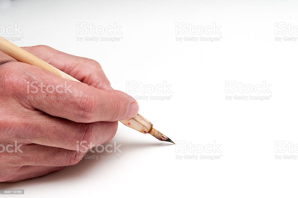Hand holding a calligraphy pen stock photo