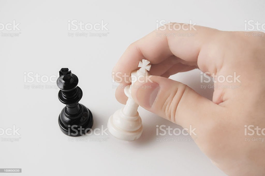 Hand holding a chess piece on white background stock photo