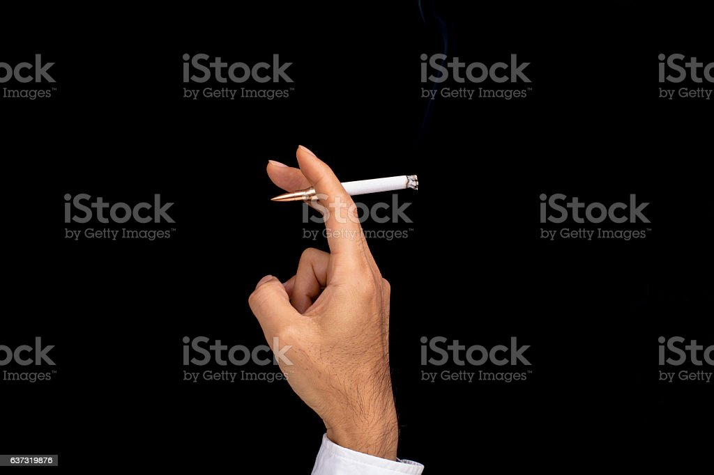 hand holding a cigarette with a bullet butt stock photo