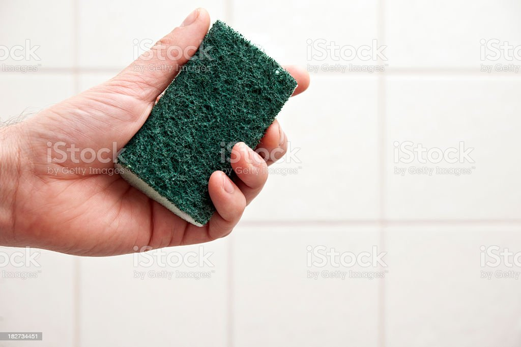 Hand holding a cleaning sponge infront of tiles stock photo