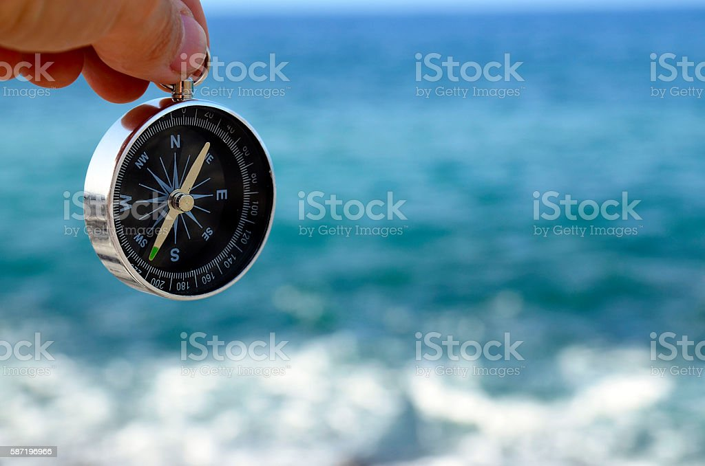 Hand holding a compass on a blue ocean background. stock photo