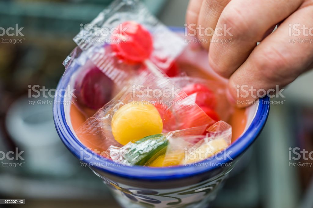 Hand holding a cup filled with plastic packaged lollipops stock photo