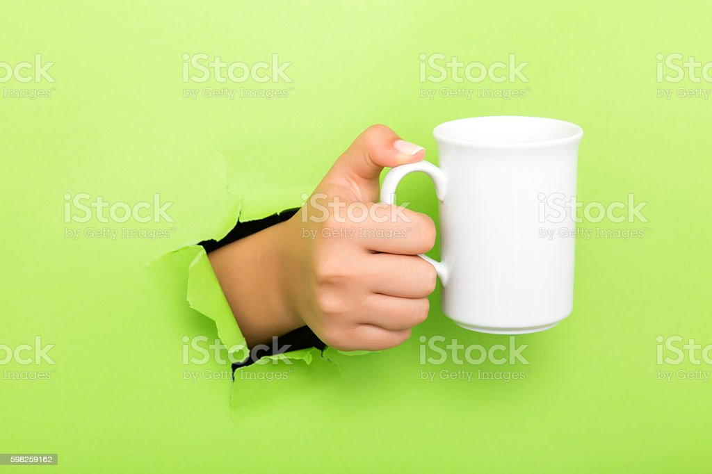 hand holding a cup through a torn white paper stock photo