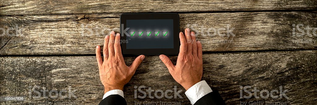 Hand holding a digital tablet with five check boxes stock photo