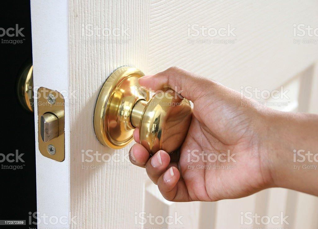 Hand holding a door knob opening a white door stock photo
