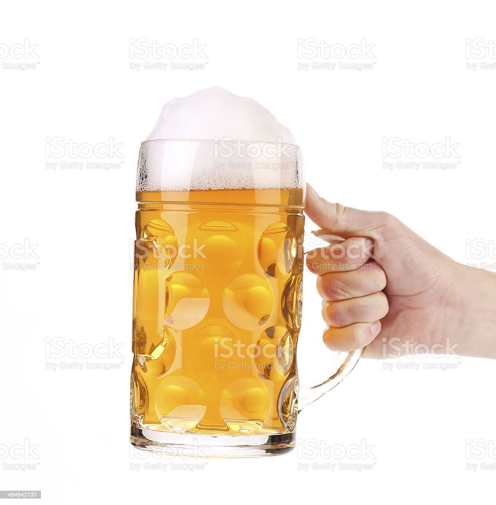 Hand holding a foaming mug of beer stock photo