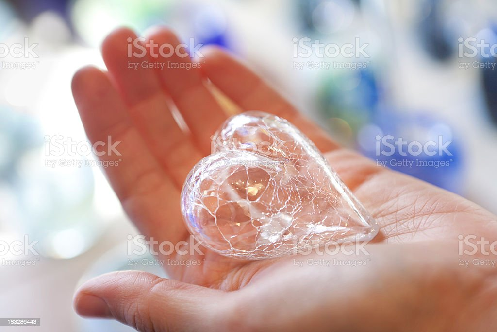 Hand holding a fragile glass heart royalty-free stock photo