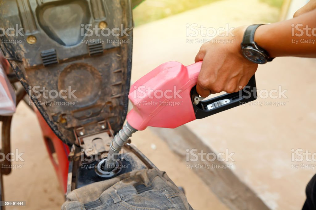 Hand holding a fuel pump at a station stock photo