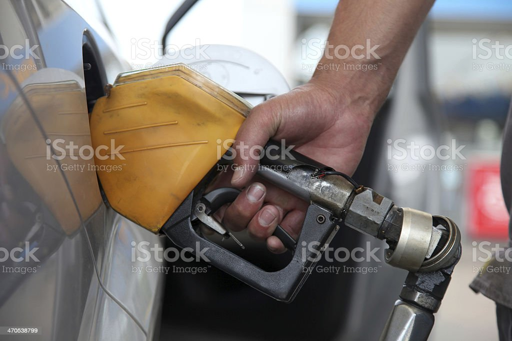 Hand holding a gas pump on gas station stock photo