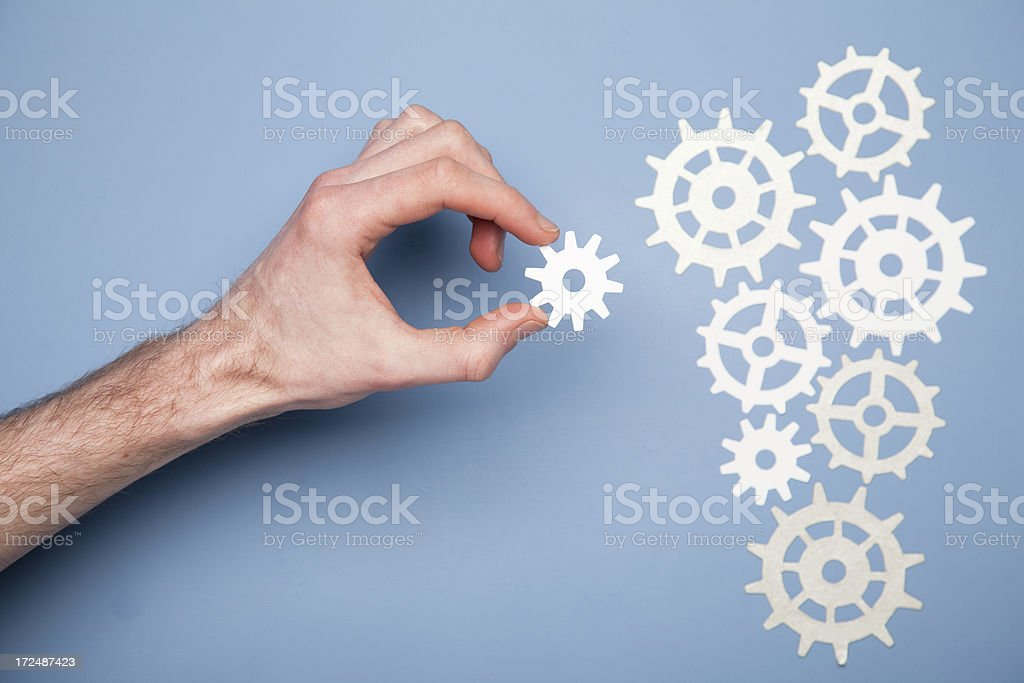 A hand holding a gear next to other gears royalty-free stock photo