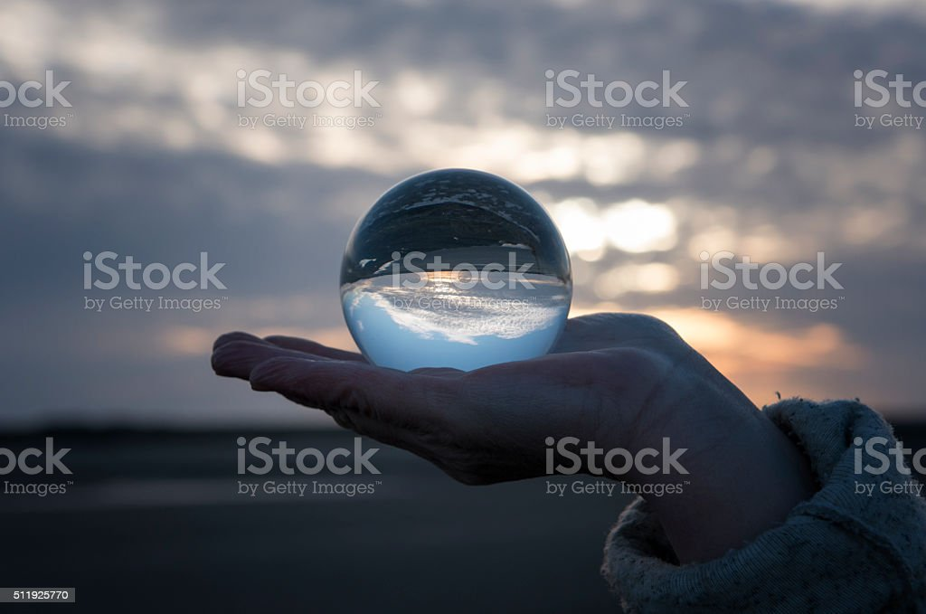 Hand holding a glass globe with reflections of a sunset stock photo