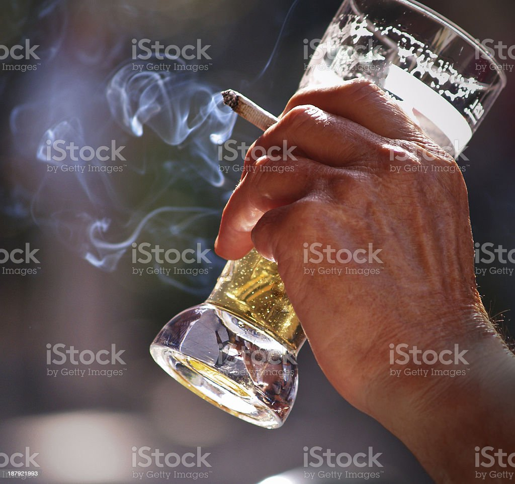 A hand holding a glass of beer and a lit cigarette stock photo