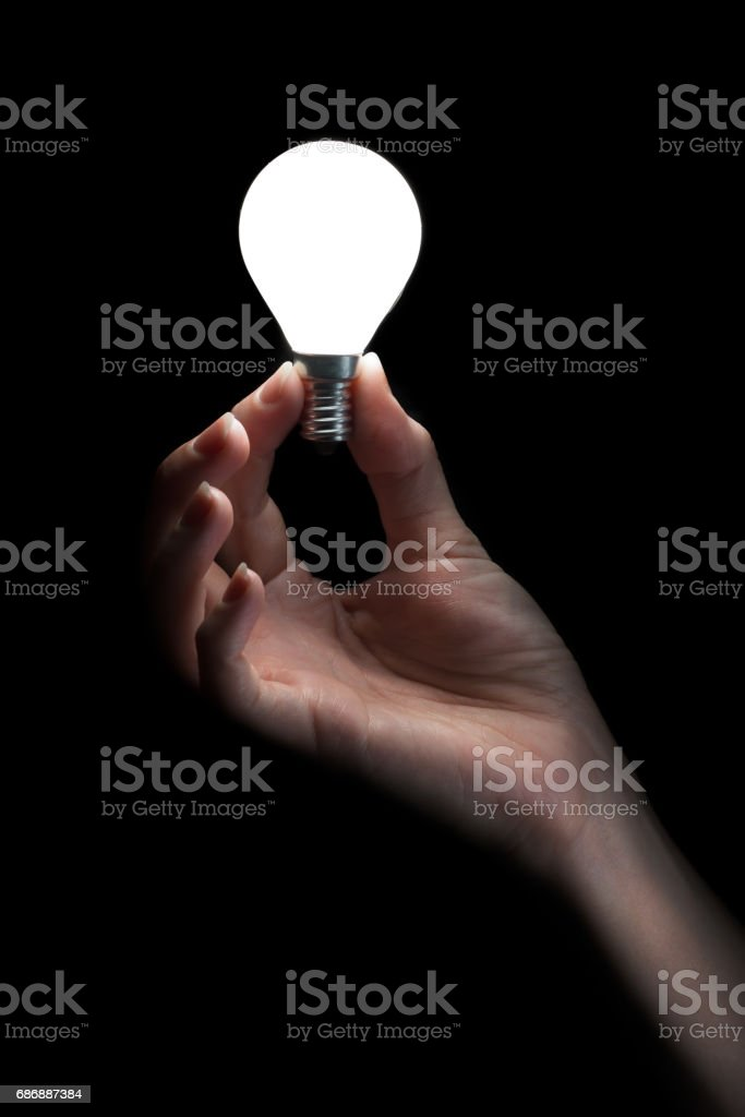 Hand holding a glowing light bulb stock photo