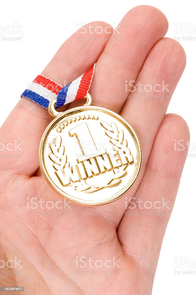 Hand holding a gold medal with ribbon royalty-free stock photo