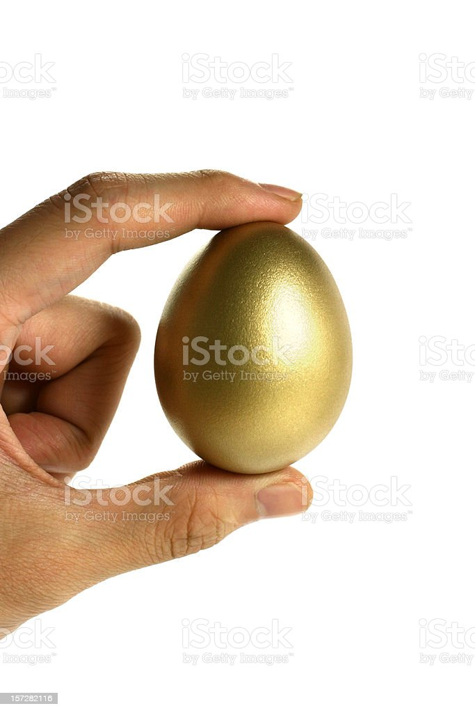 Hand Holding a Golden Egg on White Background royalty-free stock photo
