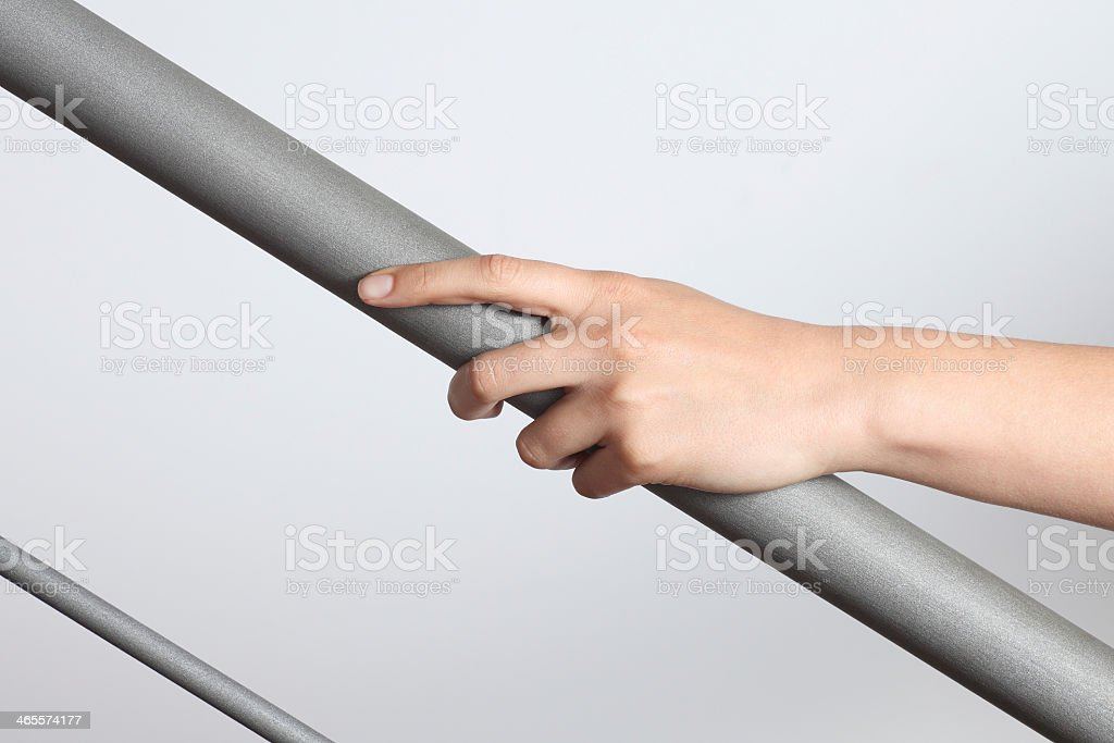 Hand holding a gray matte handrail going up, gray background stock photo