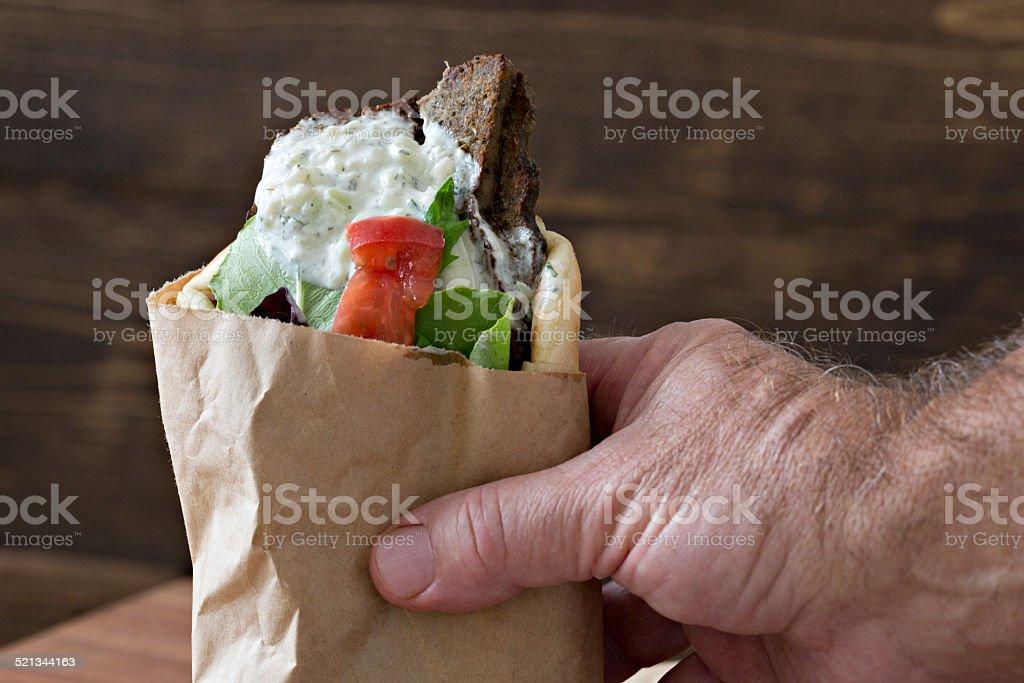 Hand Holding A Greek Gyro Sandwich stock photo