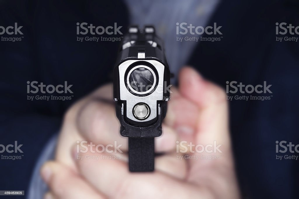 Hand holding a gun pointing straight at the camera stock photo