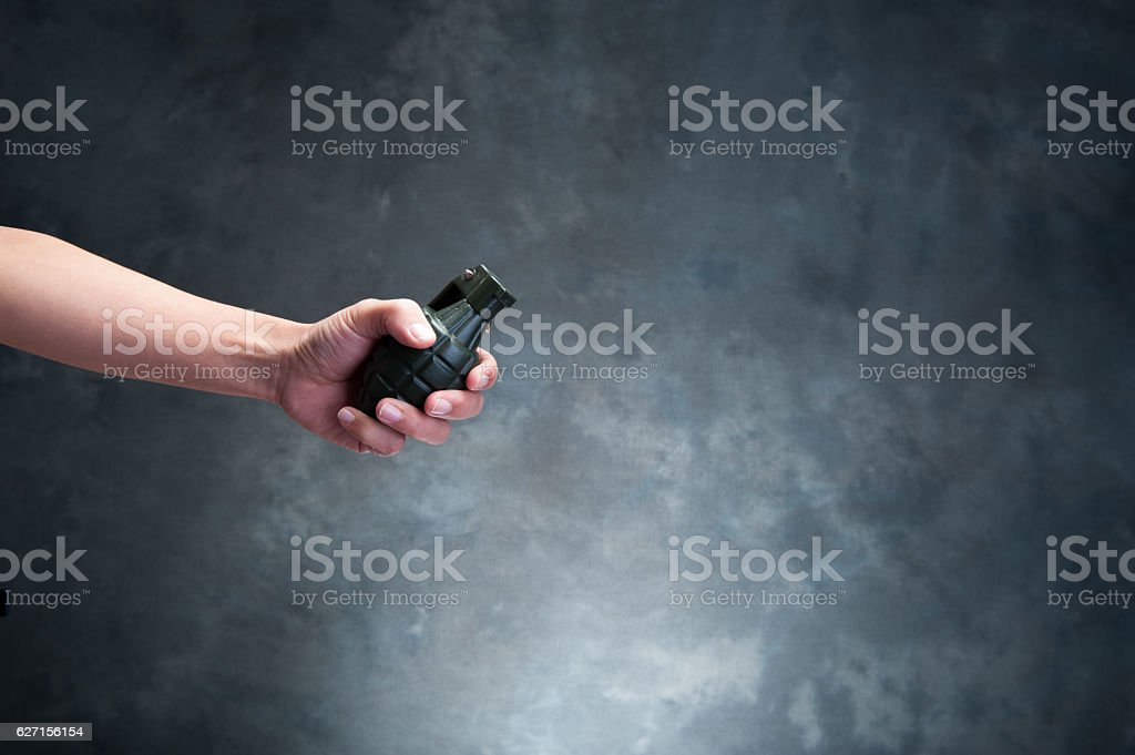 Hand holding a hand grenade stock photo