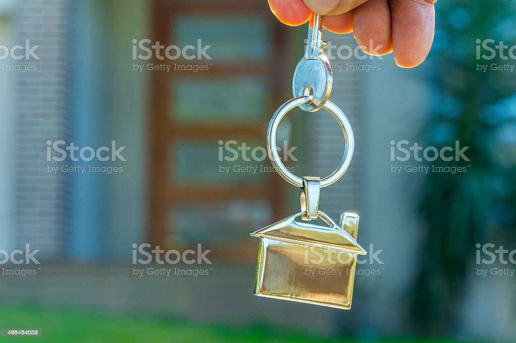 Hand holding a house key in front of a house. stock photo