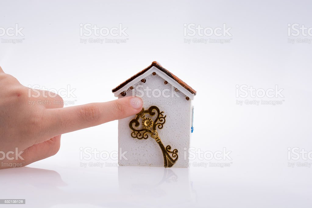 Hand holding a key near a house stock photo