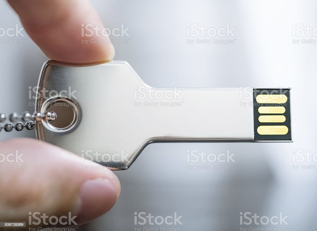 Hand holding a key shaped USB drive stock photo