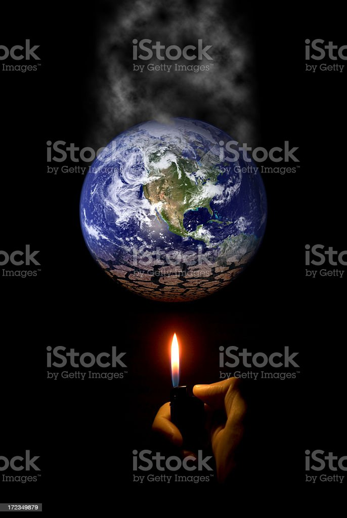 Hand holding a lighter under a globe showing global warming stock photo