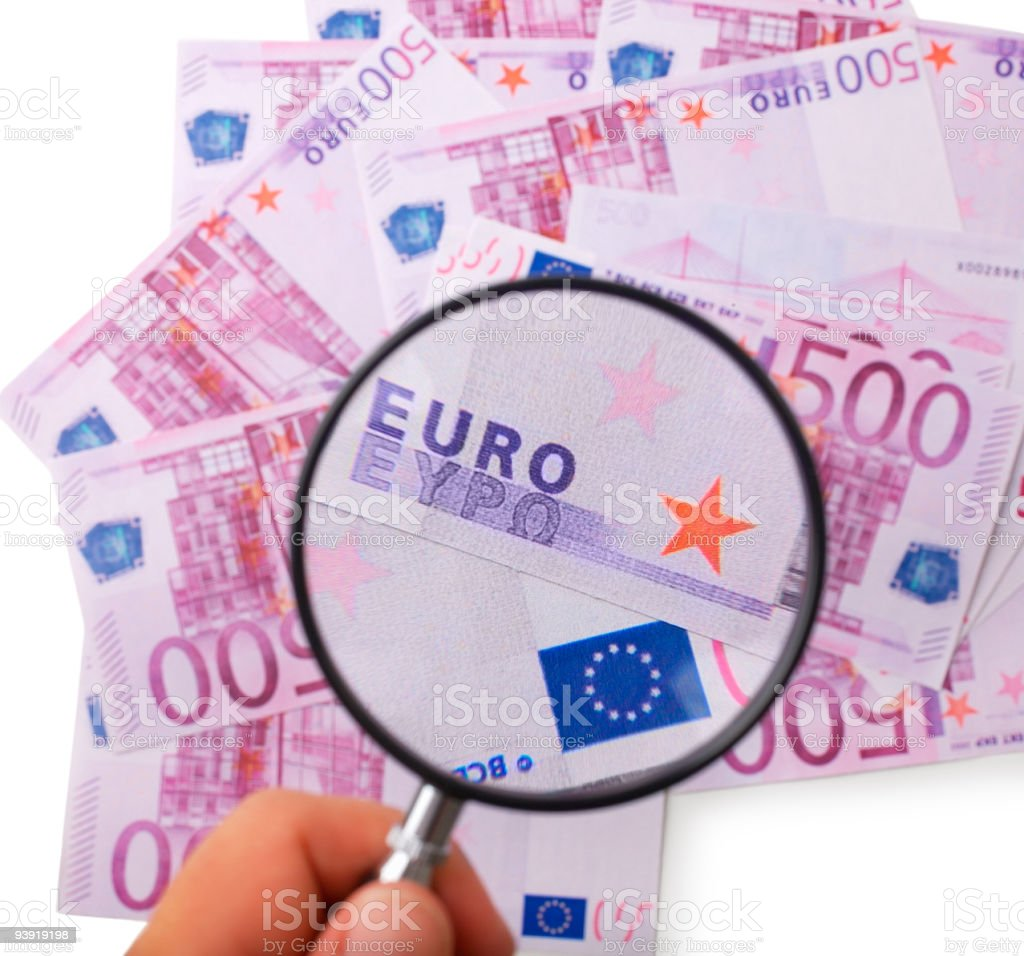Hand holding a magnifying glass over banknotes royalty-free stock photo